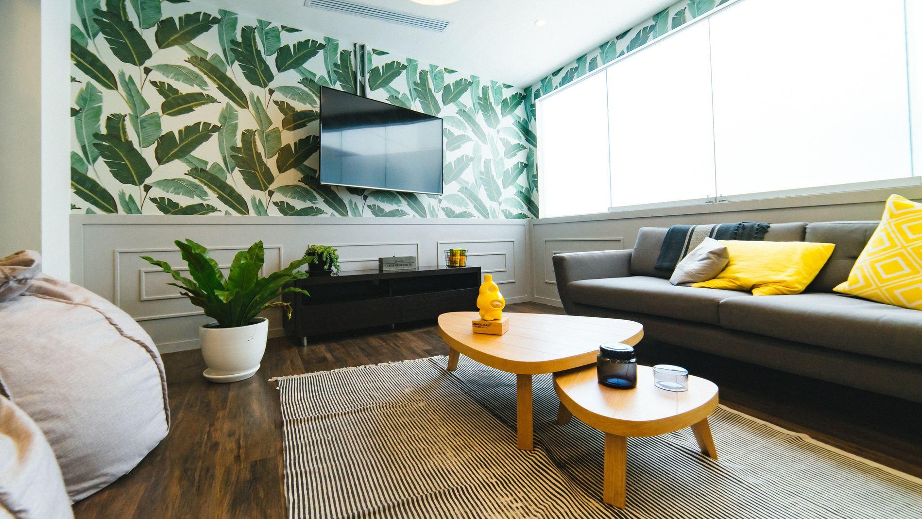 möblum uso del color e la decoración, sala con print de plantas verdes y contraste en cojines amarillos